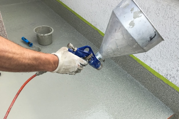 A man's hand paints the steps with a spray gun