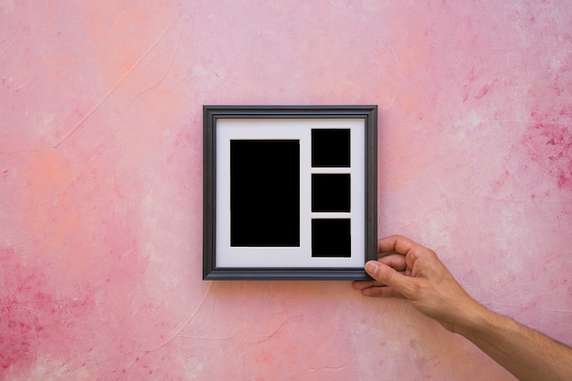 Man's hand placing picture frame on painted pink wall