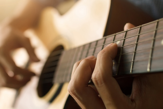 Man's hand playing acoustic guitar , musical concept