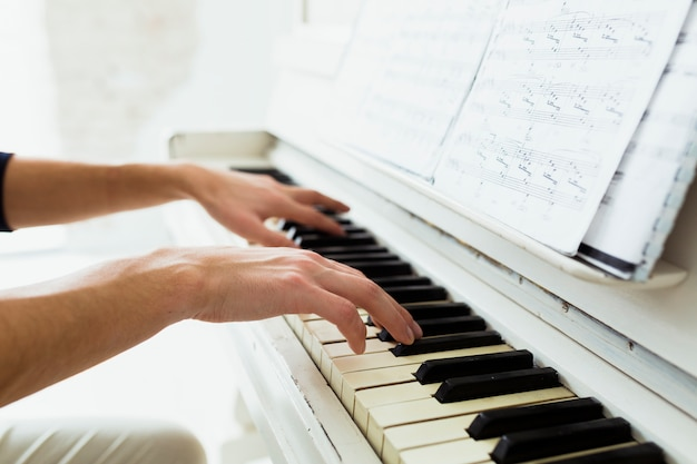 Man's hand playing piano with musical notes
