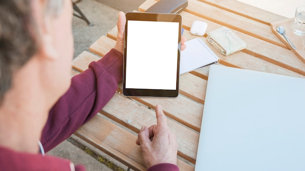Man's hand pointing finger on digital tablet displaying white screen on wooden desk