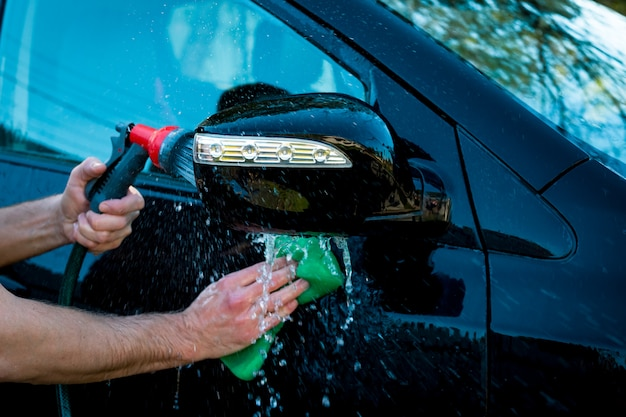 Man's hand polishing of black car by sponge and another hand hand holds the hose for washing outdoor.