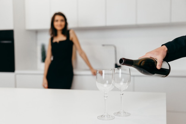 A man's hand pours red wine into glasses. woman in the background. high quality photo