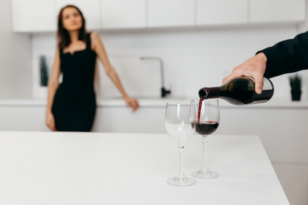 A man's hand pours red wine into glasses. woman in the background