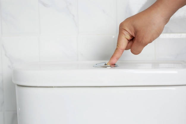 A man's hand pressing a button in the toilet