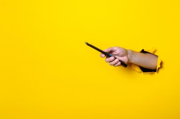 男の手が明るい黄色の背景でテレビのリモコンのボタンを押す