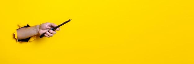 Рука человека нажимает кнопку на пульте дистанционного управления телевизора на ярко-желтом фоне