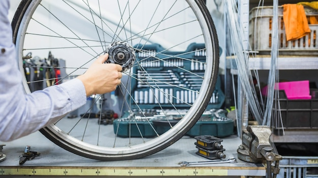 Man's hand repairing wheel of bicycle