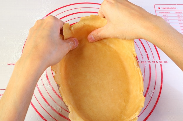 Man's hand shaping dough into the baking bowl for baking homemade pie crust