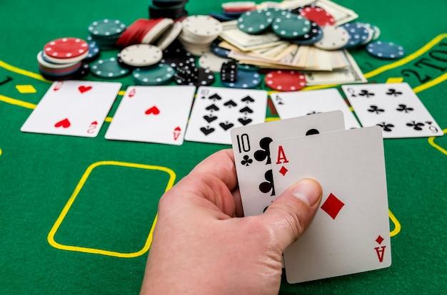 カードの組み合わせ、ギャンブルを示す男の手。