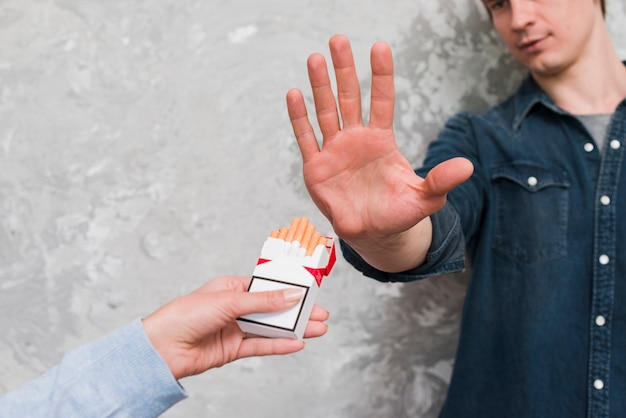 Man's hand showing stop gesturing to woman offering packet of cigarette