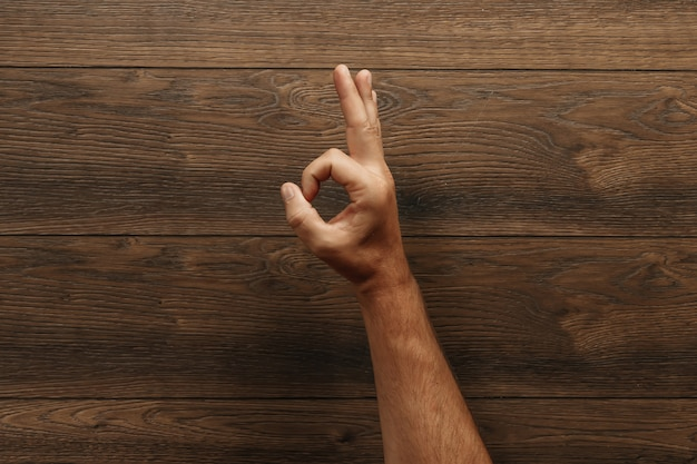 A man's hand shows ok on a wooden table