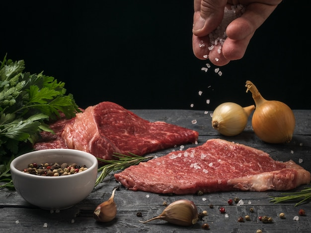 A man's hand sprinkles large sea salt on beef steaks