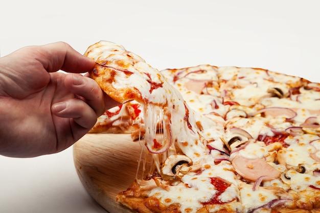 男の手は、マルガリータまたはモッツァレラチーズとマルガリータのおいしいピザのスライスを取ります