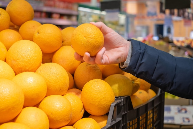 A man's hand takes a ripe orange from a box with oranges in a supermarket.