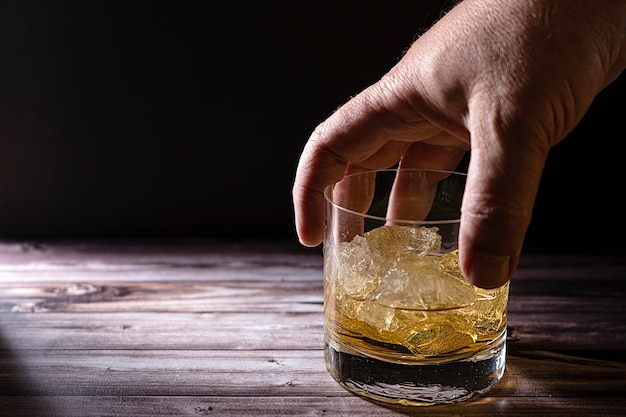 A man's hand taking a glass with whiskey or scotch and large chunks of ice on a rustic wooden table
