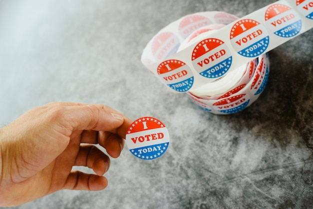 그는 오늘 미국 선거에서 스티커로 투표했다는 것을 가르치는 사람의 손.