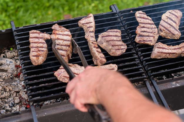 A man's hand turns over beef steaks with tongs on a charcoal grill in the garden
