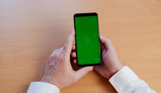 緑色の画面でモバイルスマートフォンを使用して男の手。