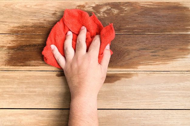 A man's hand using red rags wipe the wooden floor.