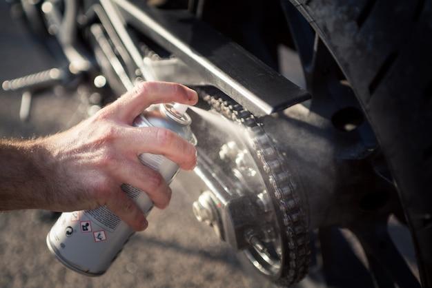 스프레이 캔을 사용하는 남자의 손은 오토바이 체인을 청소하고 보호합니다. 오토바이 체인의 유지 보수 및 윤활 개념.