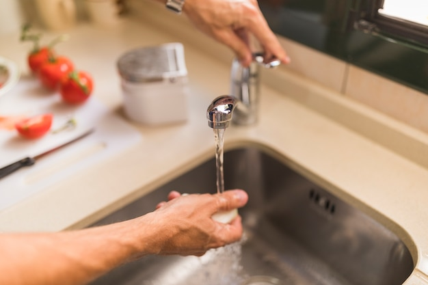 Man's hand washing radish in sink