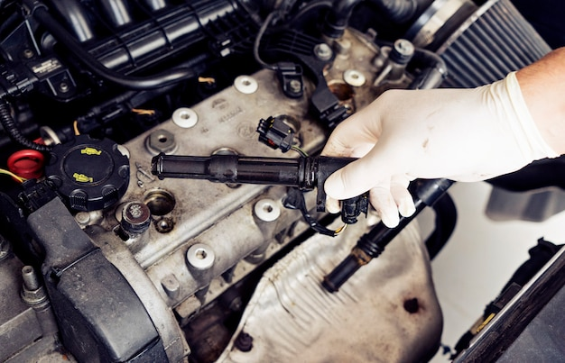 A man's hand will check the spark plugs