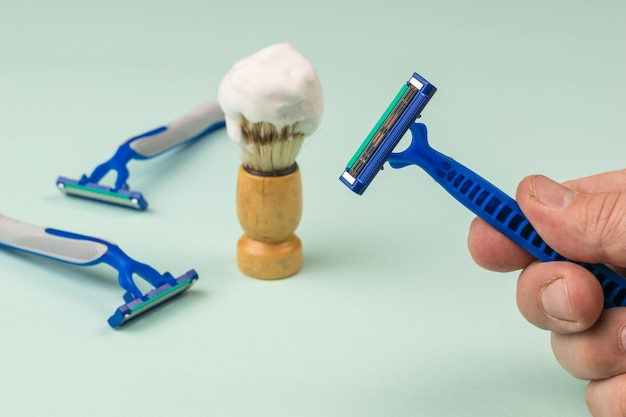 A man's hand with a disposable razor on the background of shaving accessories