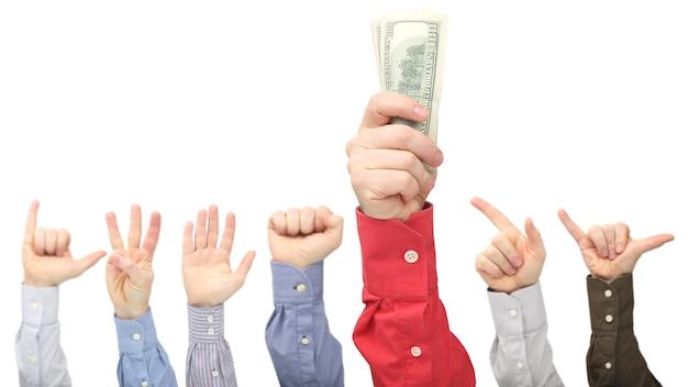 Рука человека с долларовыми купюрами на других поднятых руках