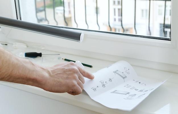 Мужская рука с инструкцией по установке рулонных штор.