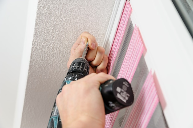 Man's hand with a screwdriver fixes the bracket of fabric blinds
