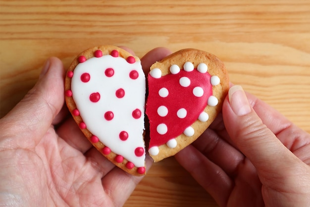Man's hand and woman's hand holding two half heart shaped cookies attach on wooden background