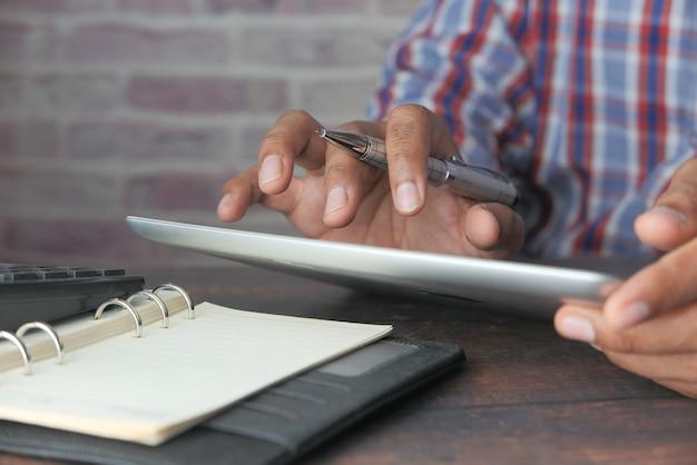 사무실 책상에서 디지털 태블릿에 노력하는 남자의 손