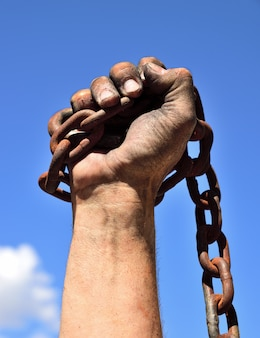 Man's hand wrapped in an iron rusty chain lifted up against a blue sky