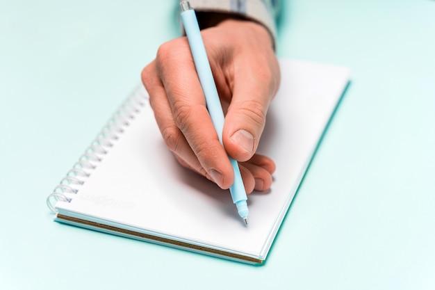 남자의 손은 노트북, 파란색 배경에 미니멀리즘에 씁니다.