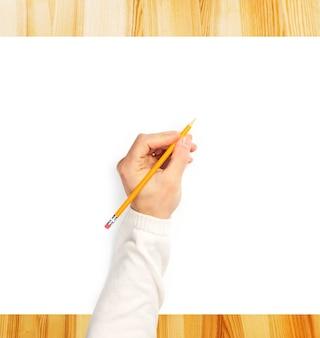 木製の机の上の白い紙に書く人間の手
