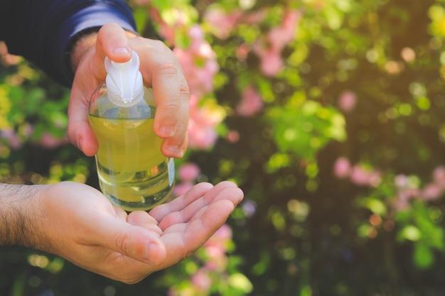 自然のcopyspaceで彼女の手に消毒剤を適用する男の手