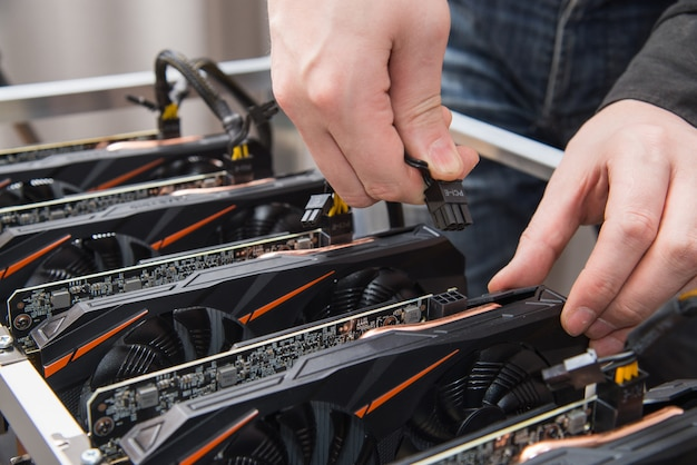 Man's hands connecting a new graphics card to mining farm. it equipment. cryptocurrency business.