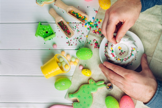 Man's hands decorating easter cake with sugar sprinkles