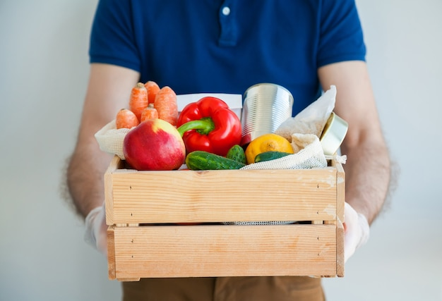 Man's hands in gloves holding food box