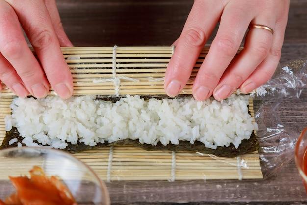 남자의 손을 잡고 대나무 매트. 대나무 매트와 요리 보드. 요리사가 맛있는 초밥을 만듭니다.