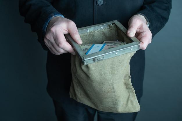Руки человека, держа сумку банка, полную денег