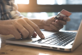 Man's hands holding a credit card and using laptop computer for online shopping