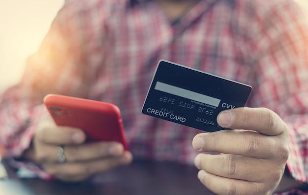クレジットカードを持ってオンラインショッピングにスマートフォンを使用している男の手。有料およびオンラインショッピング用のクレジットカード。オンライン支払いの概念。コーヒーショップで働いているフリーランサー。