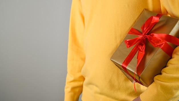 赤い弓でギフトボックスを保持している男の手