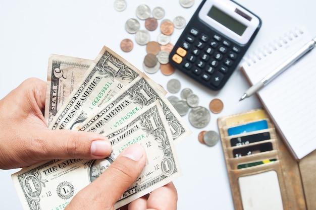테이블에 지갑에 동전과 신용 카드로 지폐를 들고 남자의 손