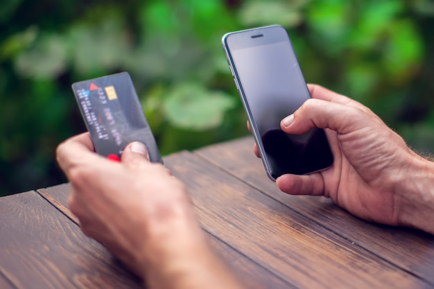 Man's hands holding a credit card and using smart phone for online payment