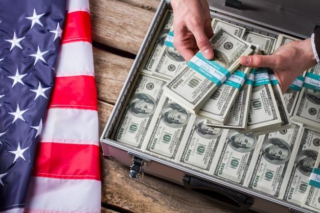 Мужские руки, держа пачки долларов. флаг сша, руки и наличные деньги. лучшая мотивация для губернатора. работайте усерднее и зарабатывайте больше.