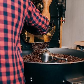 현대적인 커피 로스팅 기계 위에 갓 볶은 향기로운 커피 콩을 들고 있는 남자의 손.