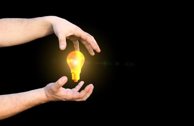 電球を持っている男の手。電気使用の概念。黒の背景に分離。